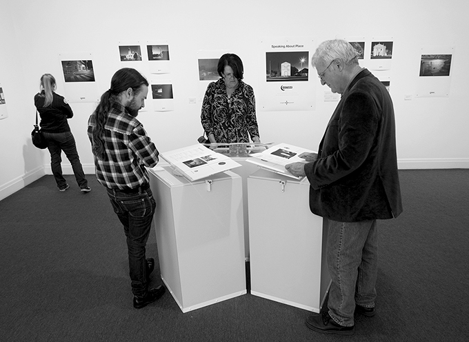 Exhibition viewers reading Facebook responses