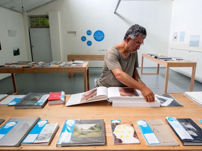 Peter Lyssiotis looking at an Aperture Book